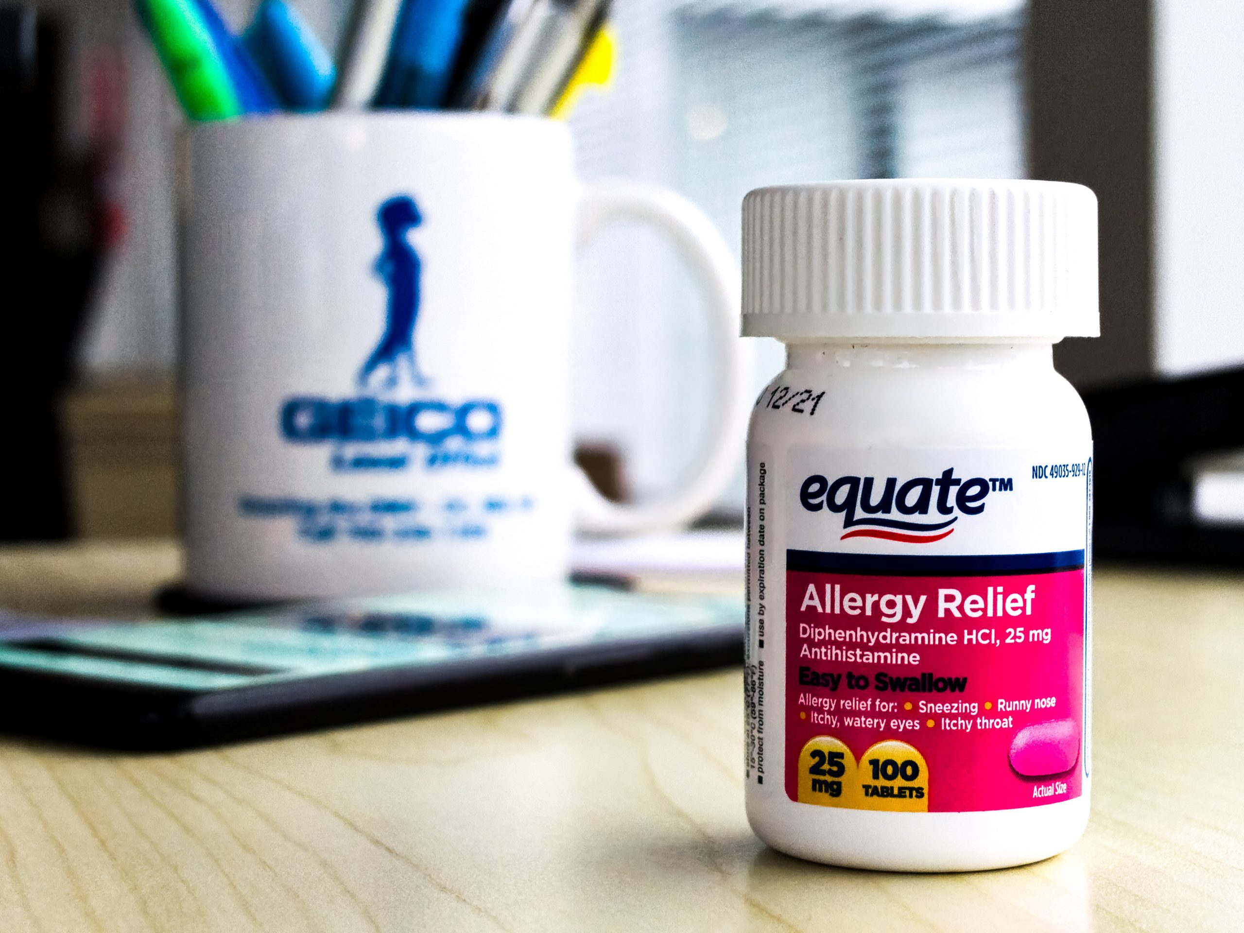 A bottle of equate brand allergy medicine on an office desk in daylight, with a Geico mug and Google Pixel 3XL in the background.