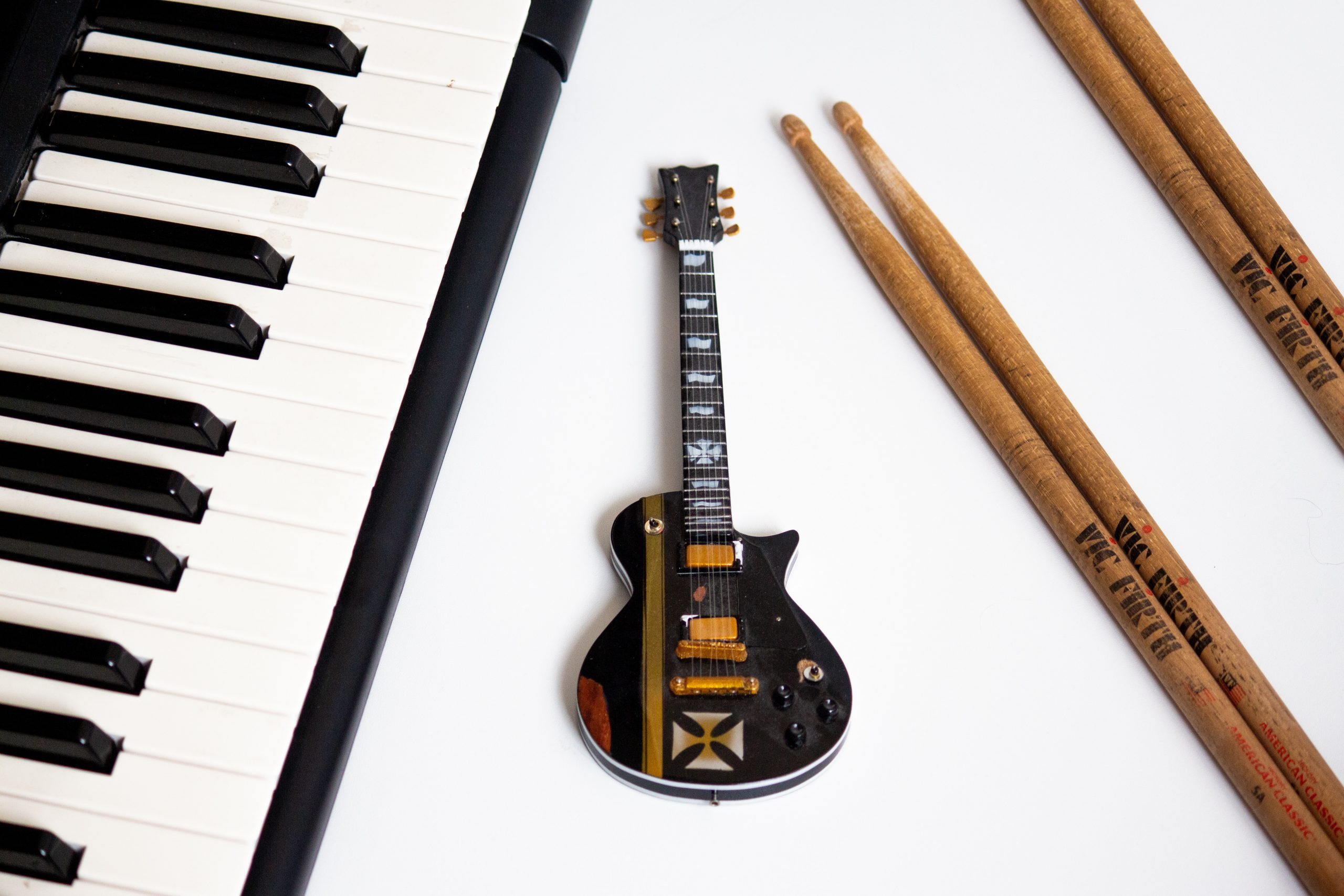 black electric guitar on white surface
