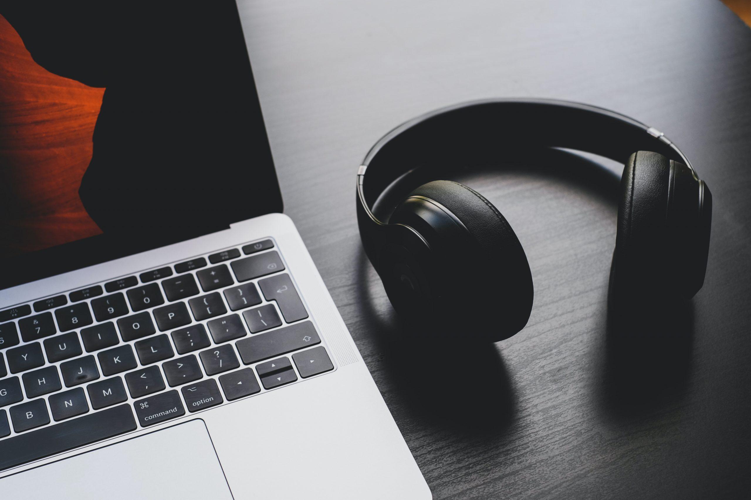 black wireless headphones beside MacBook Pro