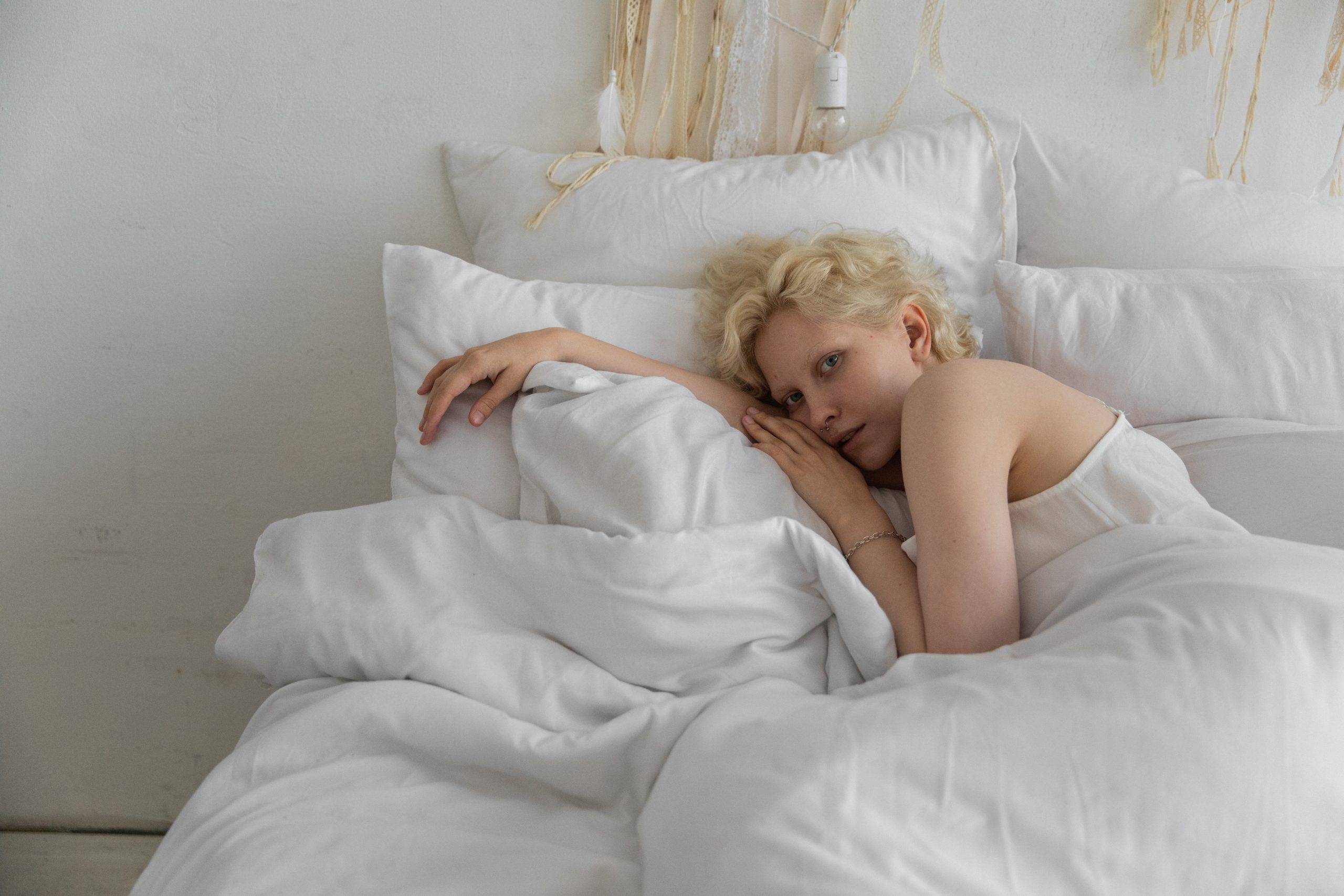 Calm woman lying on comfortable pillows in bedroom