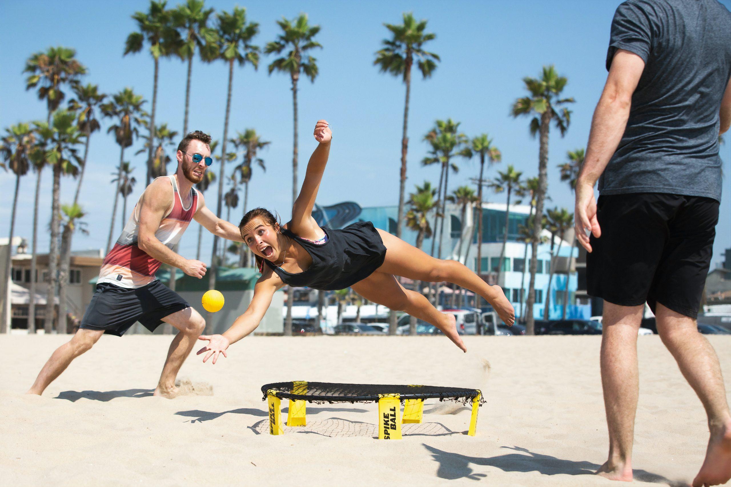 Girl diving for ball over Spikeball net on the beach