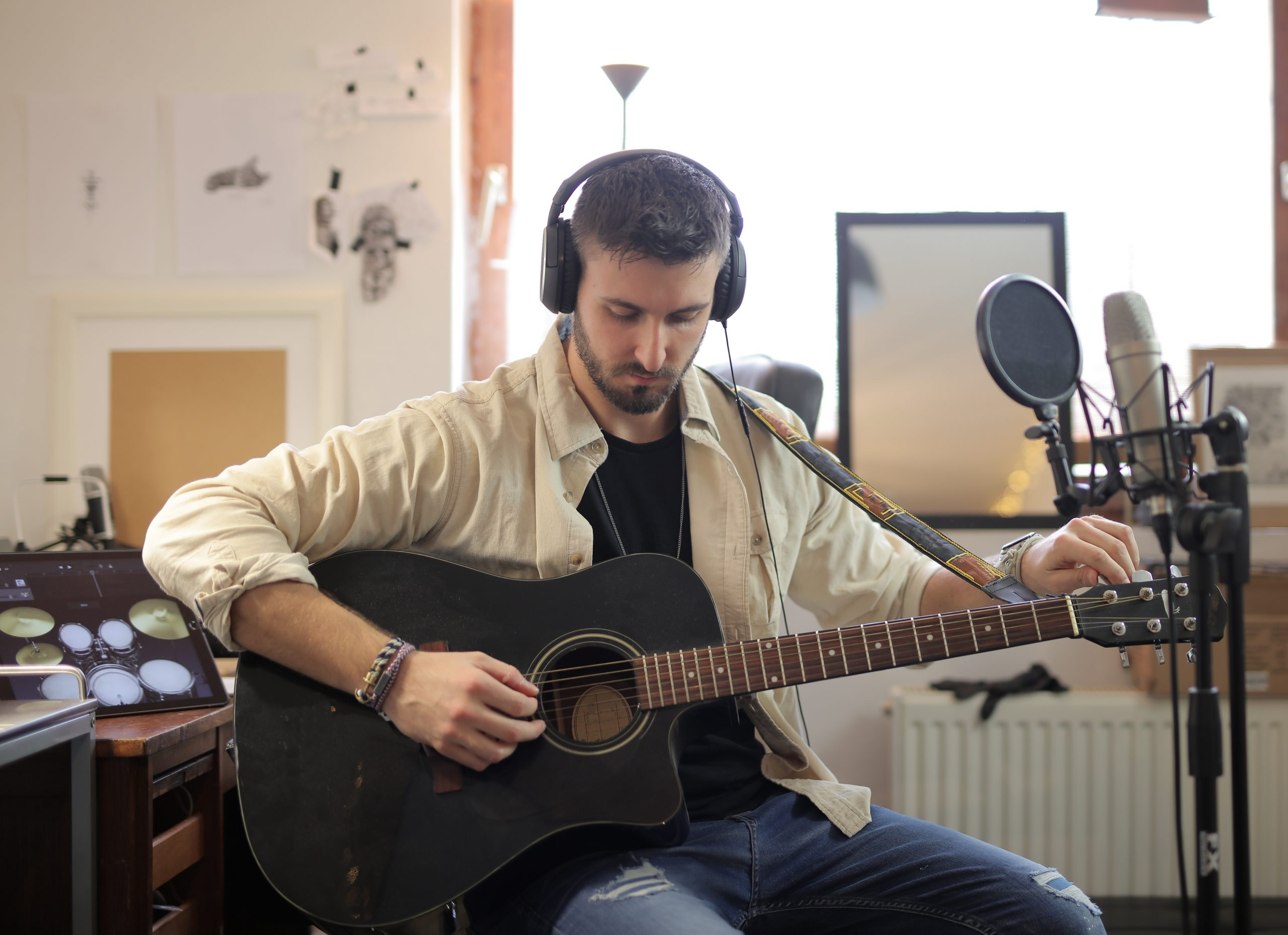 Man in beige dress shirt tuning acoustic guitar