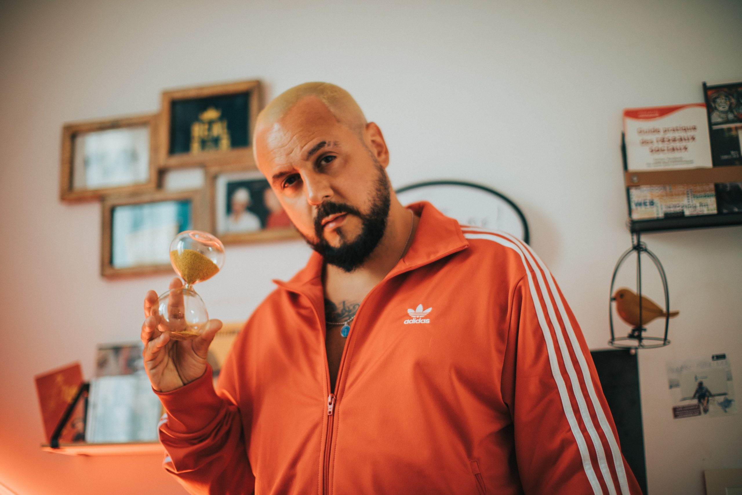 man in red adidas zip up jacket holding clear glass ball