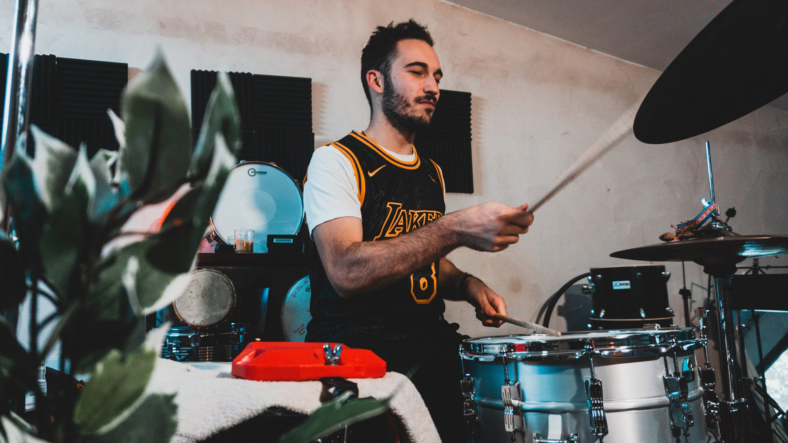 man in white and blue crew neck t-shirt playing drum