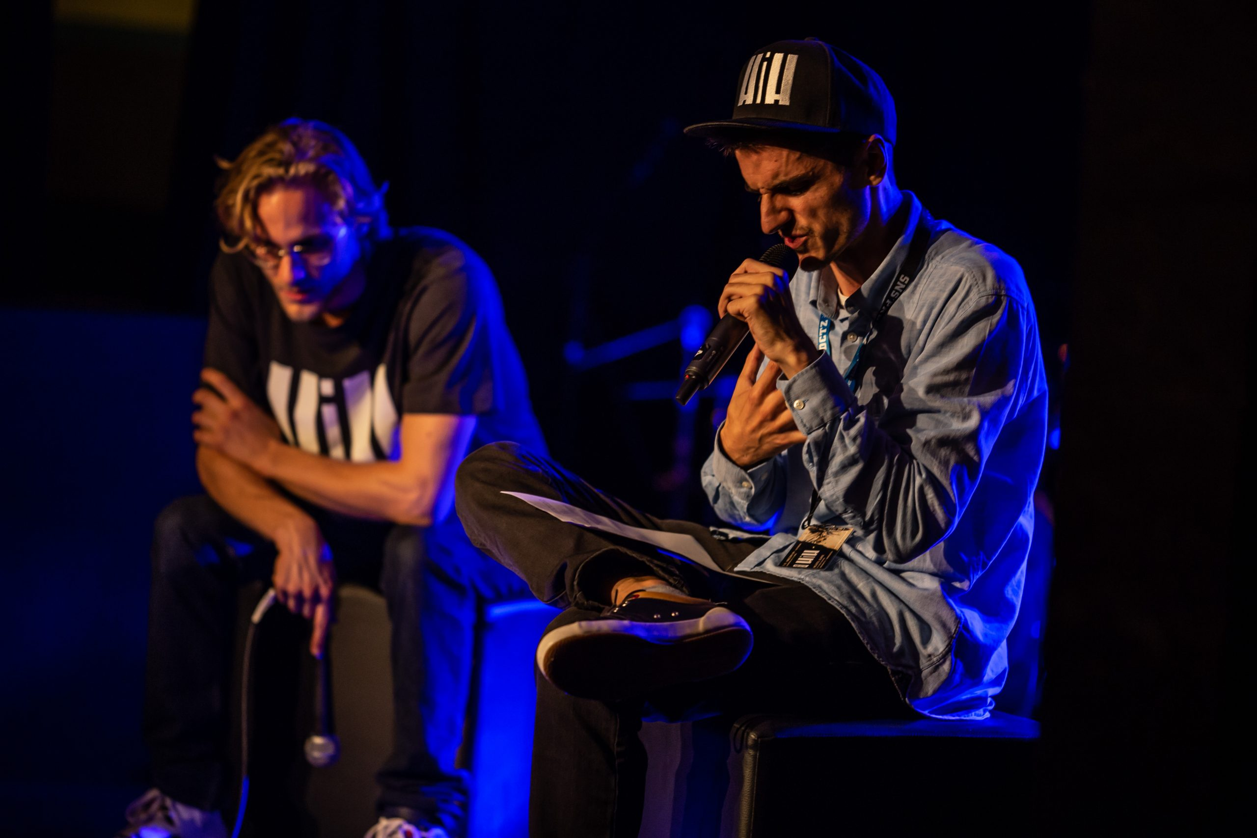 Man sitting on ottoman holding microphone