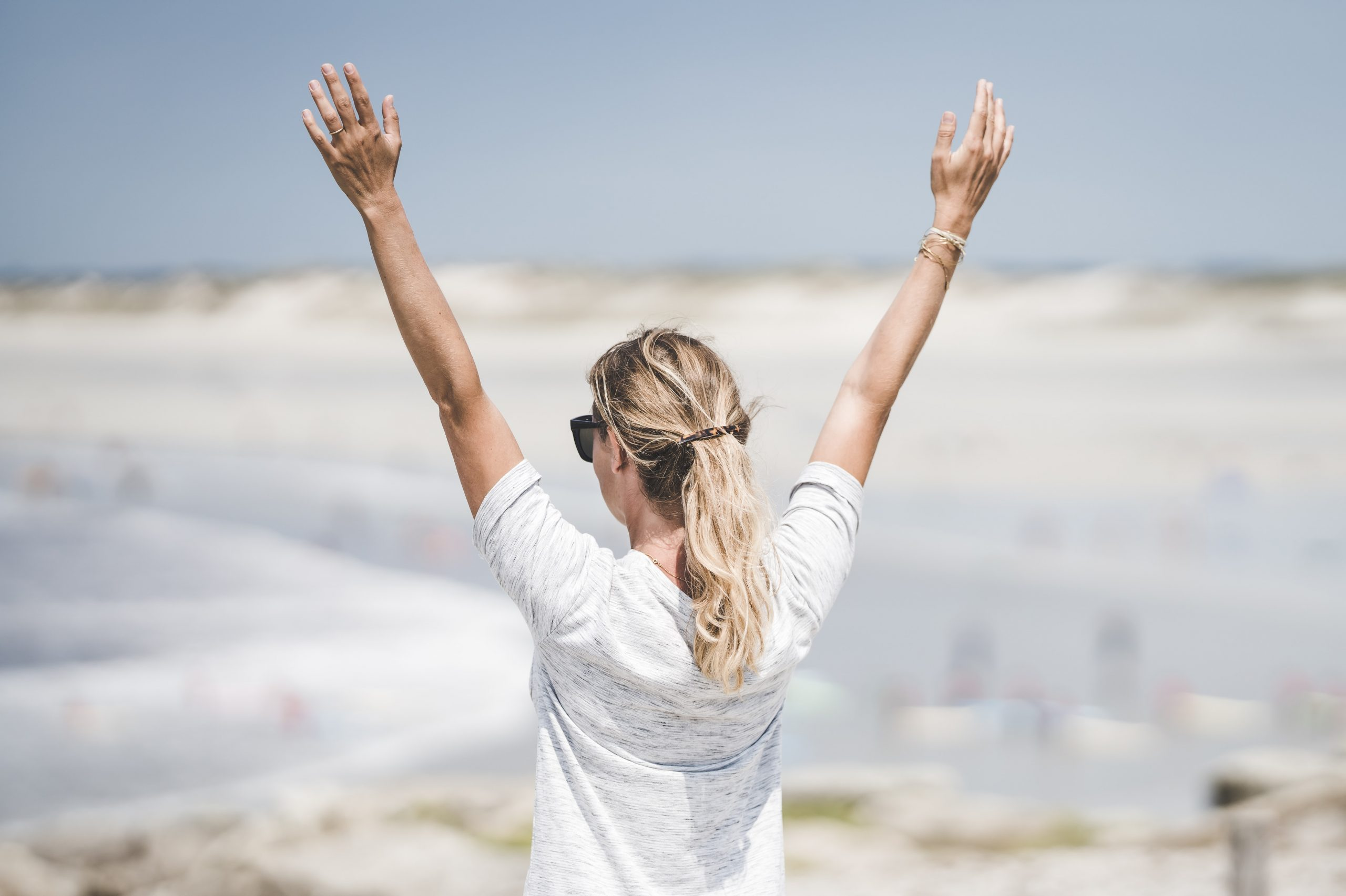 woman in white long sleeve shirt raising her hands