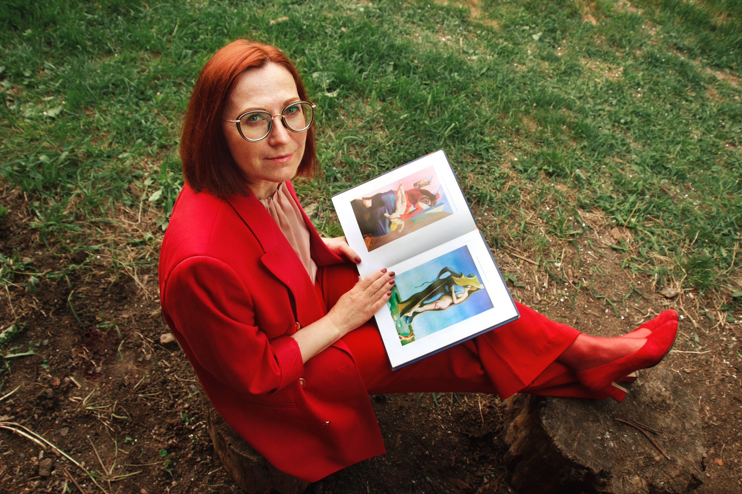 An elegant aging woman in her mid-50s wearing a red pant suit and sitting in her courtyard. Middle-aged woman holding an illustrated book about fine art.