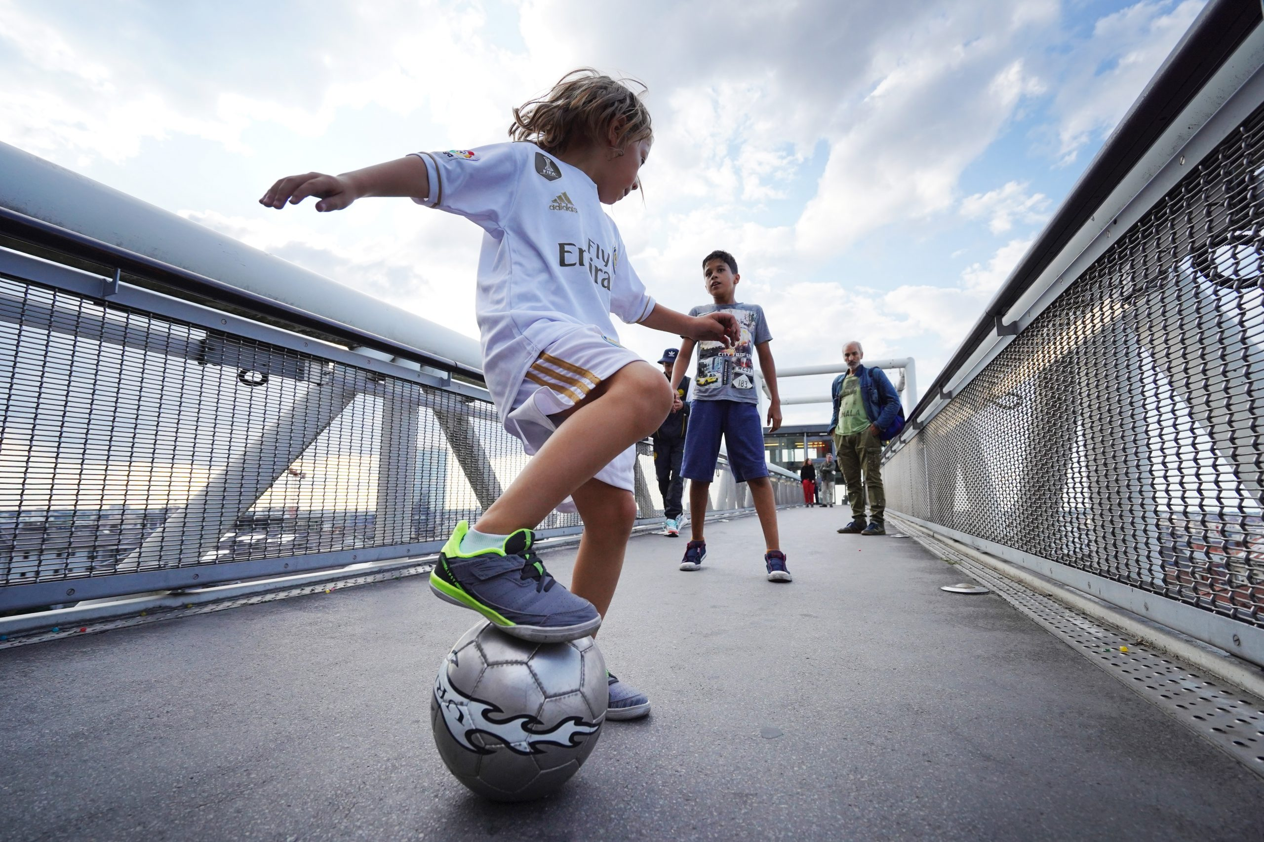 boy in white t-shirt and blue shorts playing soccer during daytime