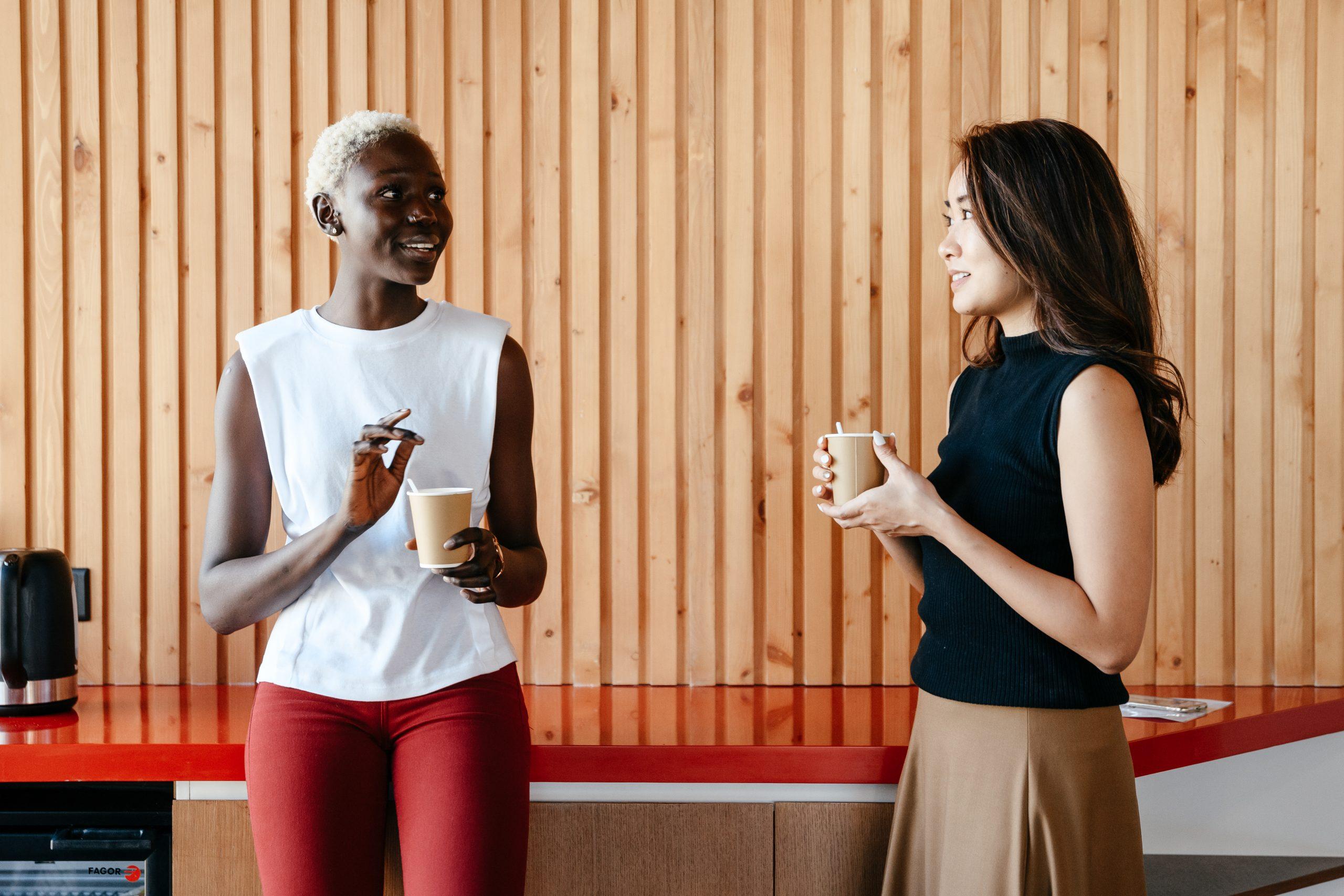 Diverse women with takeaway coffee in office