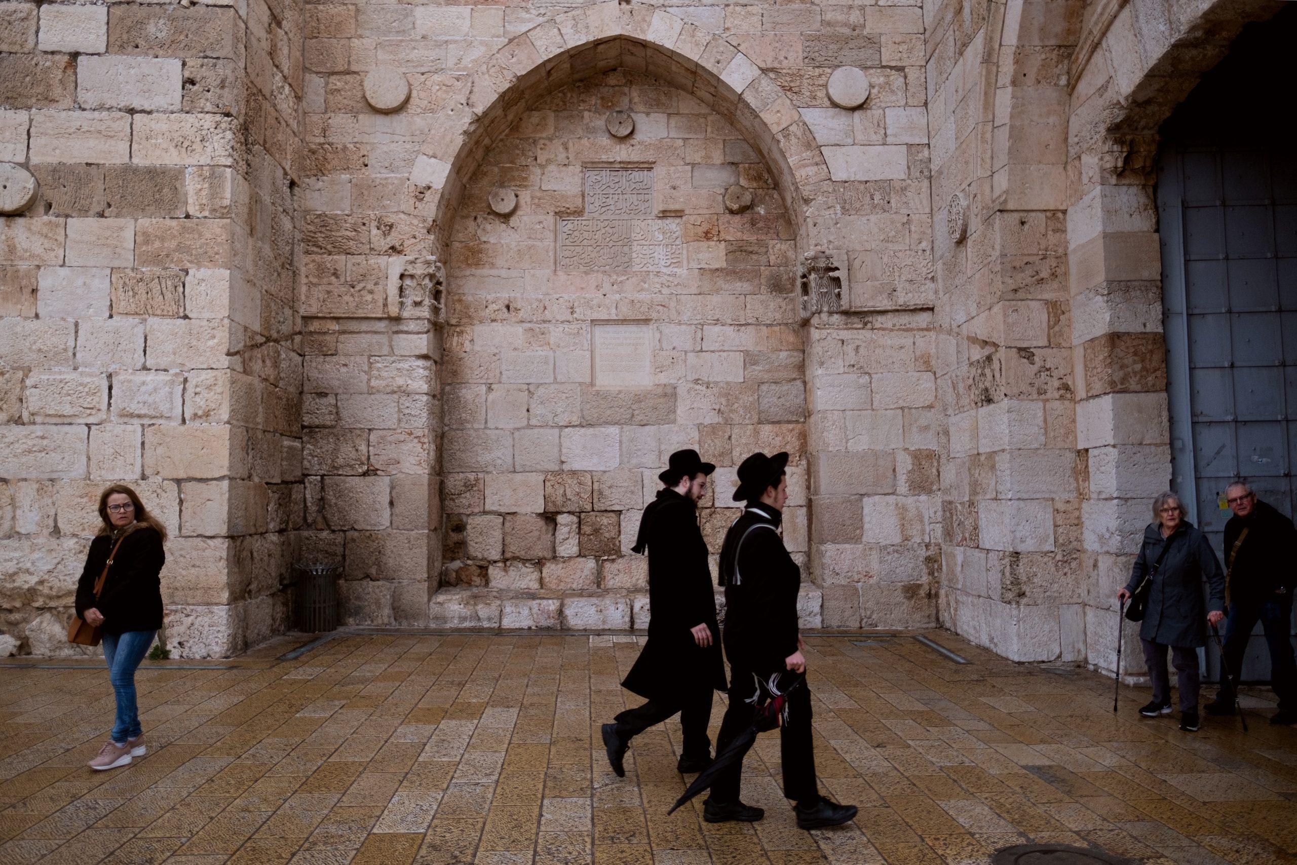 Haredim walk toward the Jaffa Gate into the Old City of Jerusalem, past a set of ancient Ottoman inscriptions.