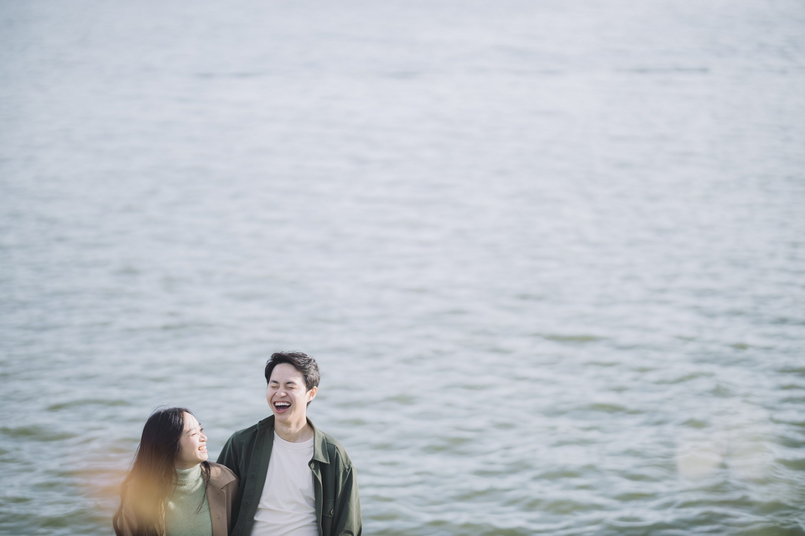 man and woman smiling beside body of water during daytime