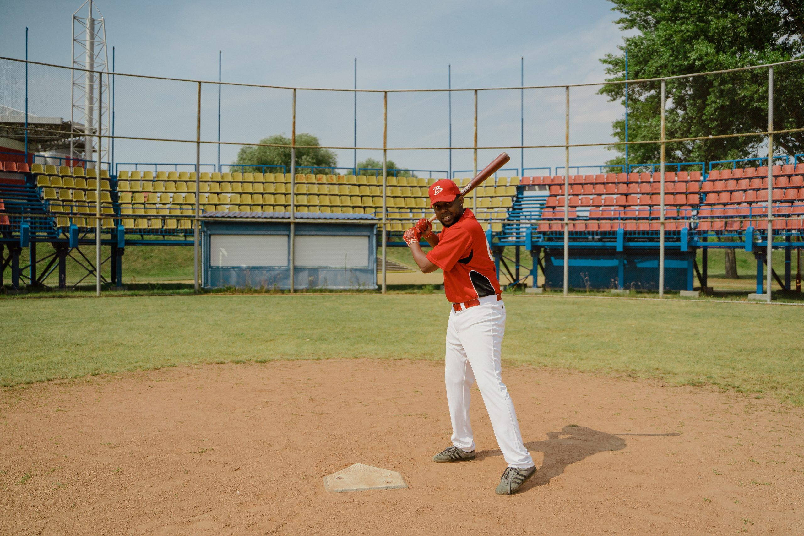 Man in red shirt and white pants playing baseball
