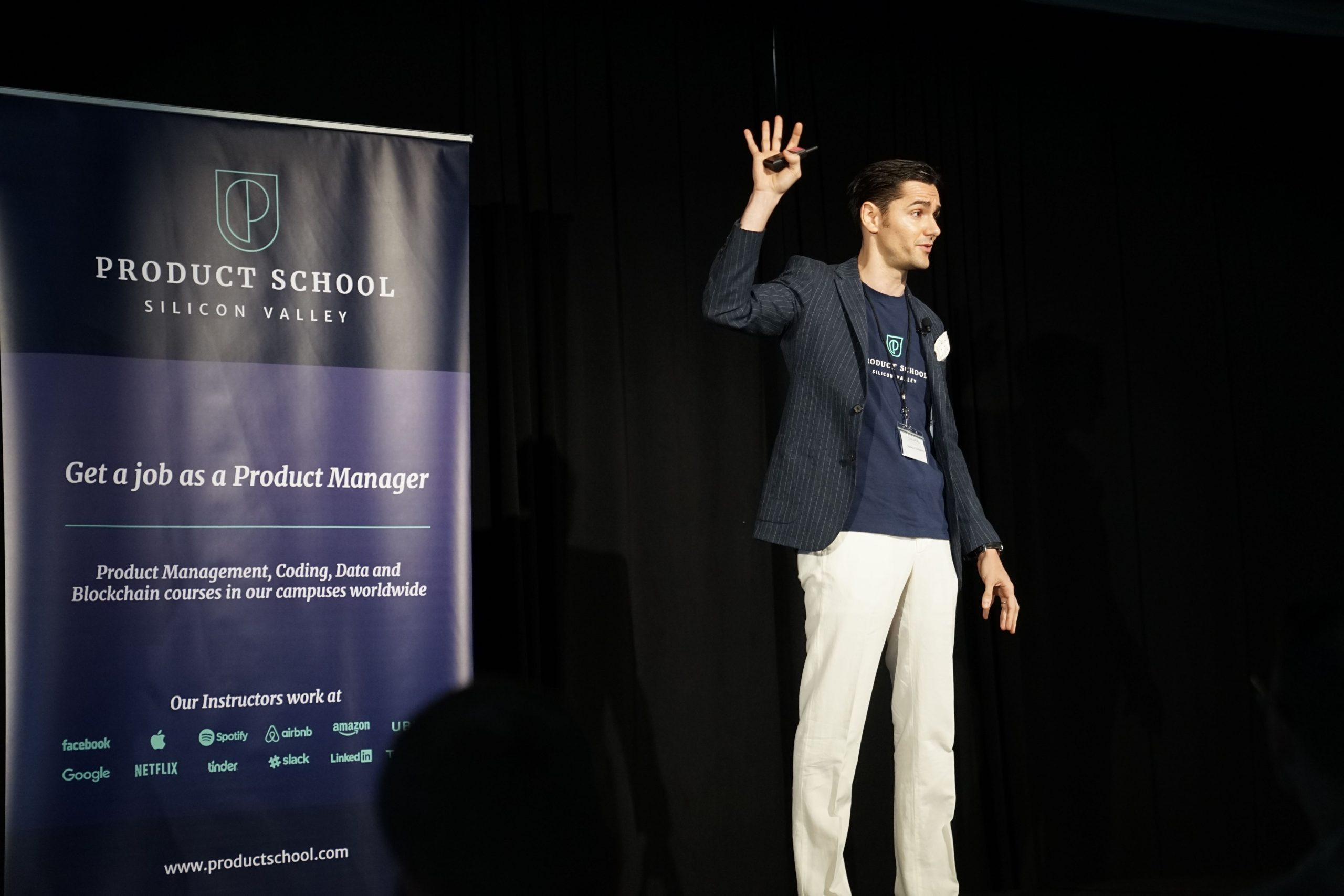 Man raising his hand during a presentation at a conference on stage