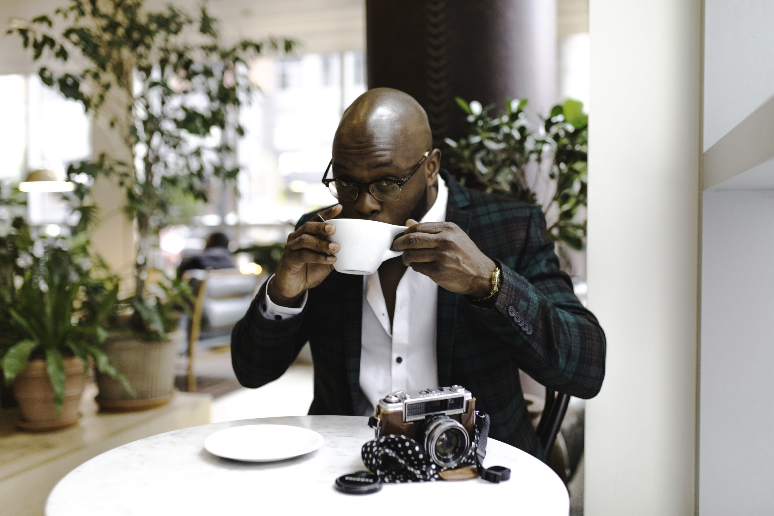 Man sitting in front of round table while sipping from white ceramic mug