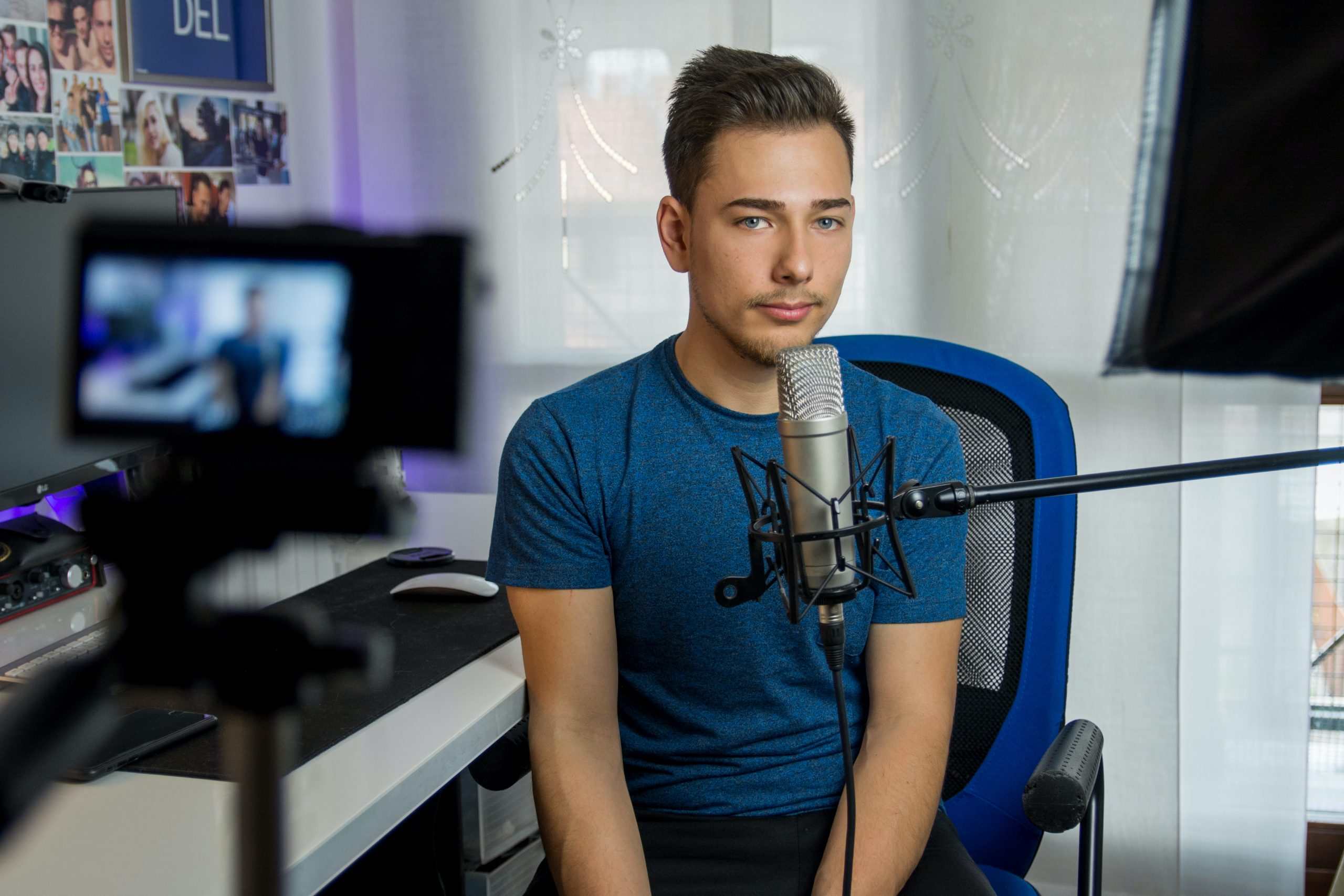 man sitting on chair in front of condenser microphone