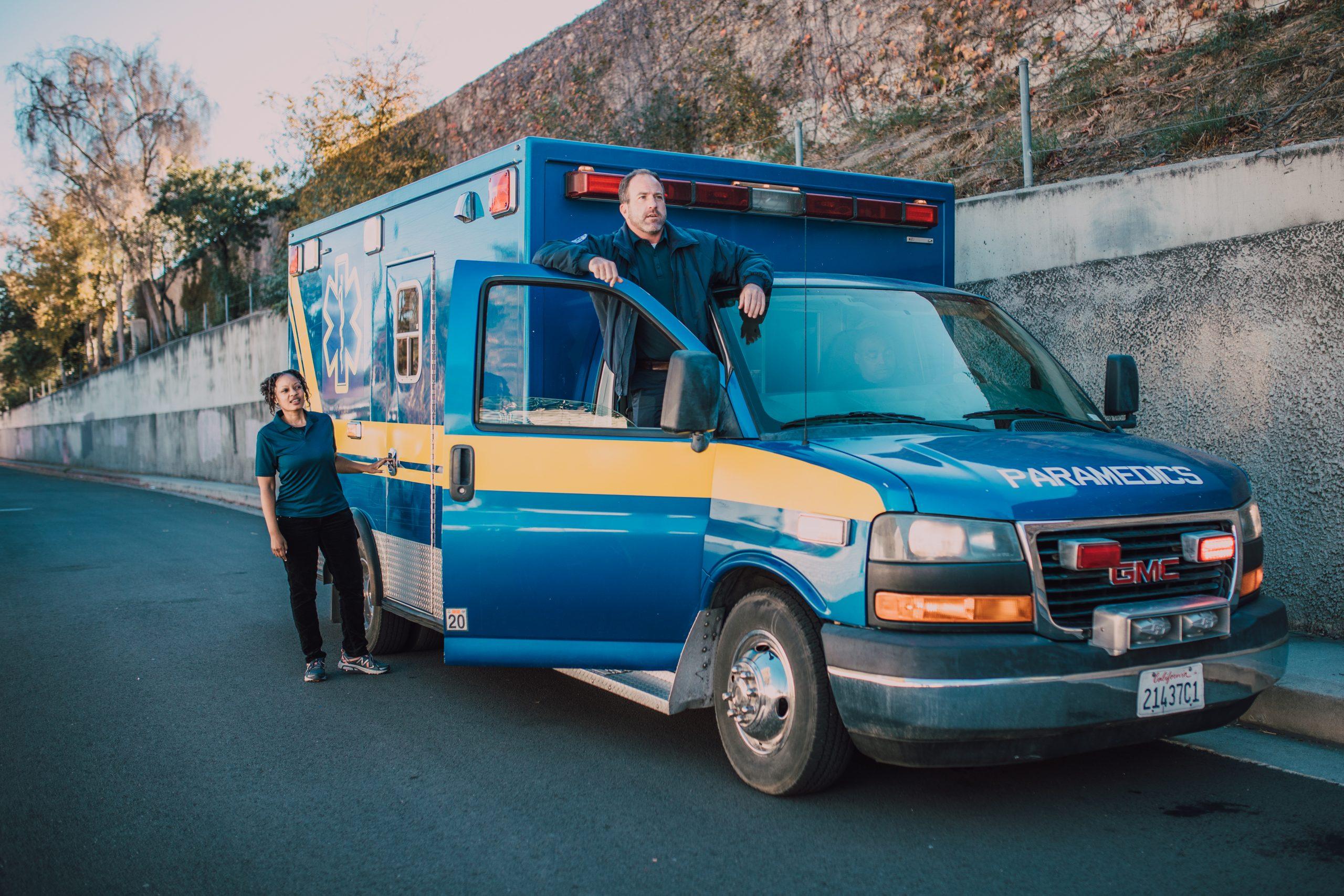 Man standing on ambulance door