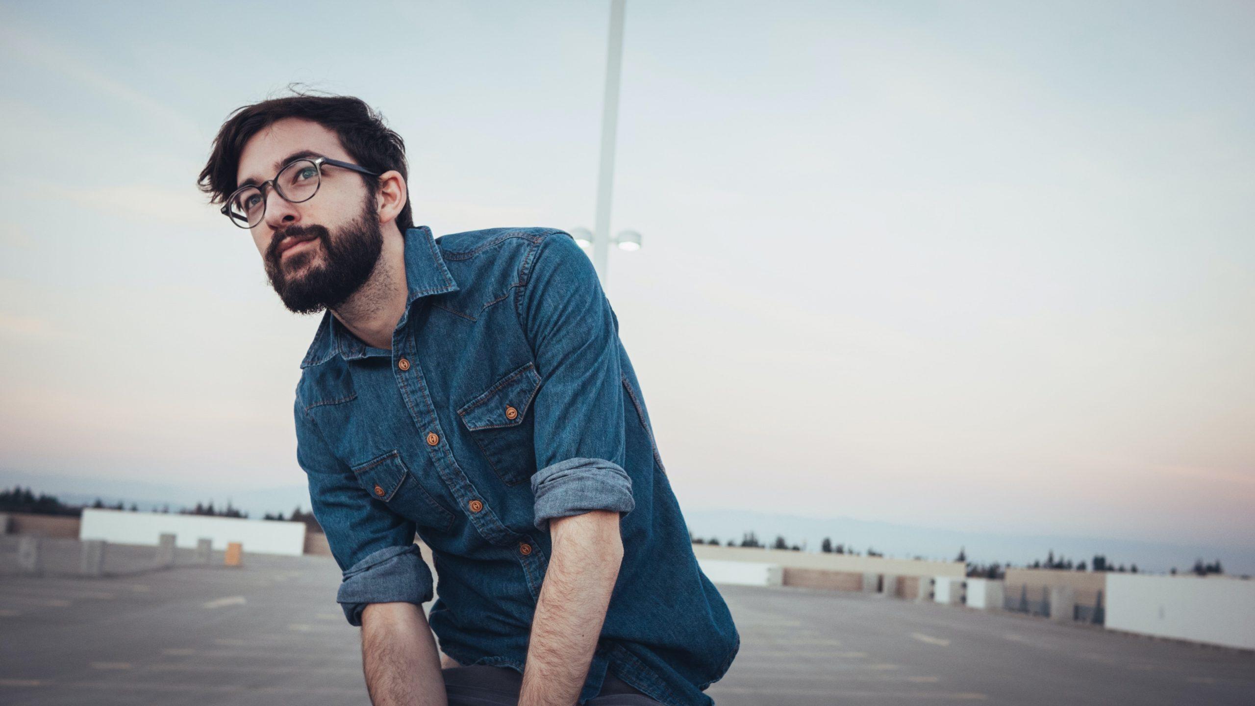 man wearing denim sport shirt and sunglasses on concrete flooring