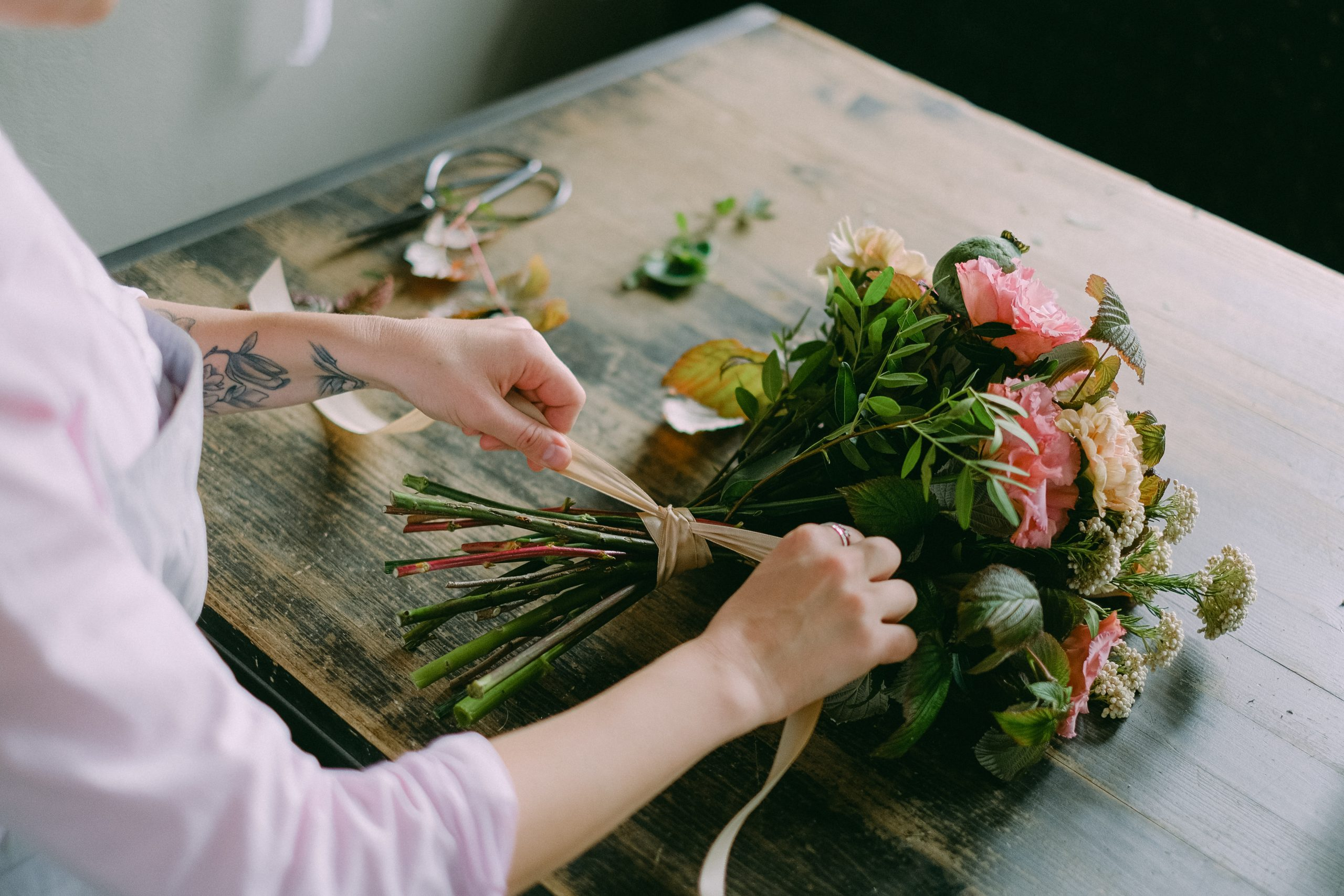 Person arranging a bouquet of flowers