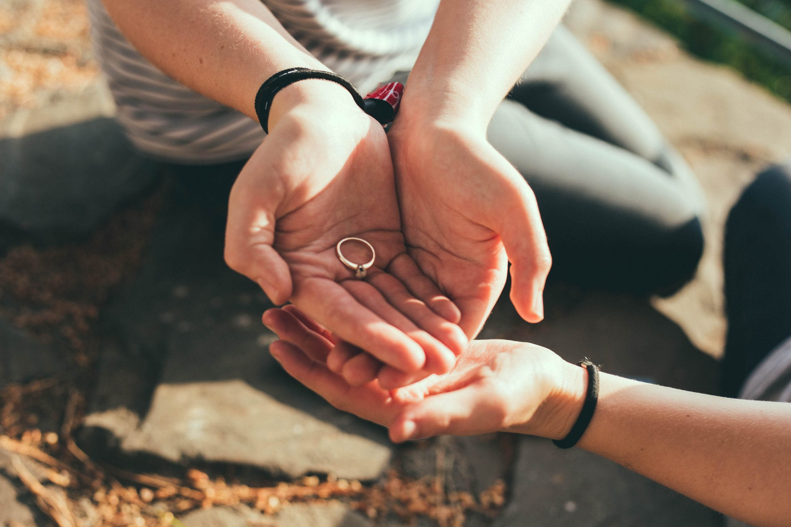 person giving ring to another hand during daytime