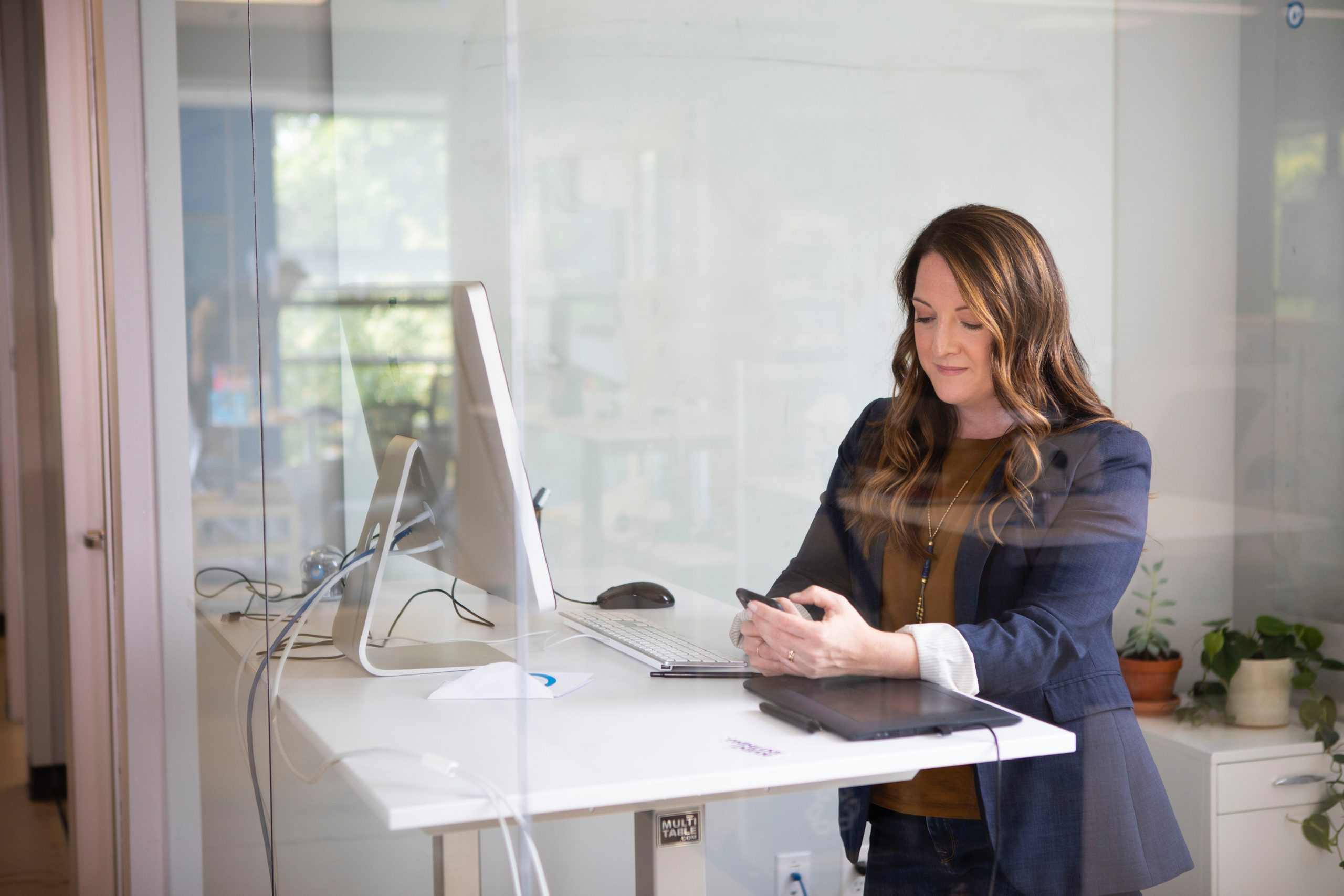 Sales woman checking her phone standing at desk with laptop