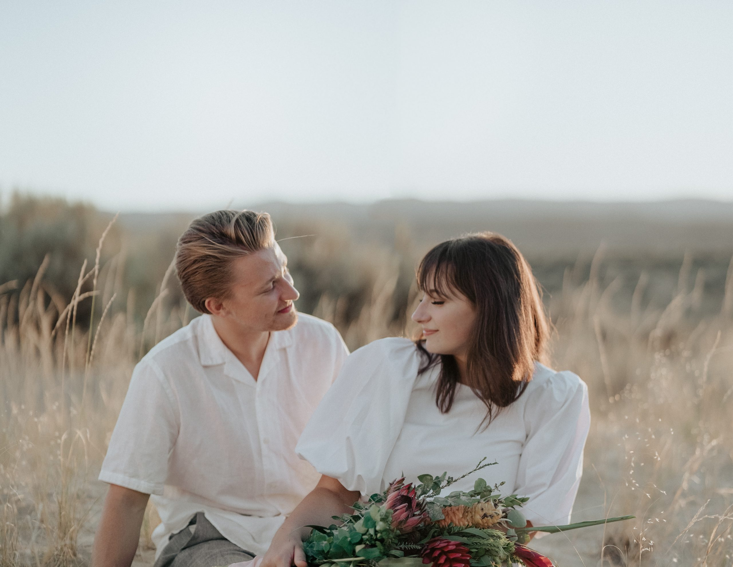 Smiling couple on grassy meadow in nature
